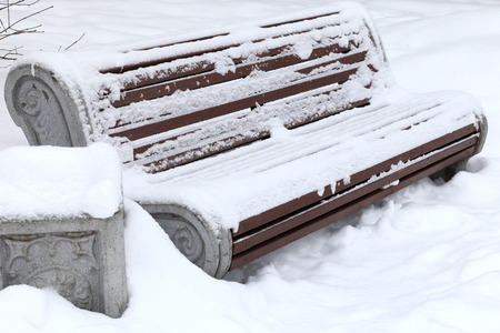Bench in the snow at the winter park photo