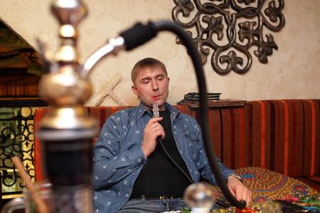 person smoking: Persona hookah fumar en el restaurante asi�tico