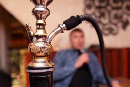 person smoking: Persona shisha de fumar en el restaurante asi�tico