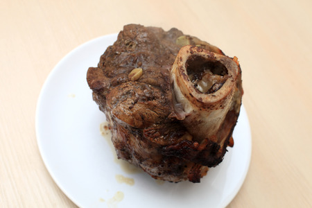 shin bone: Plate with baked beef shin on a table Stock Photo