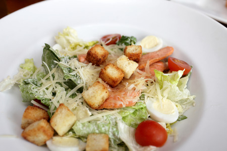 Caesar salad with fish on a white plate photo