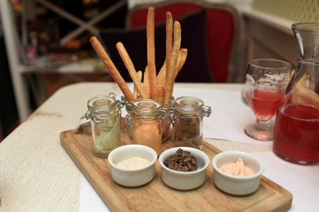 breadstick: Vegetable and meat pates with a breadstick on the table