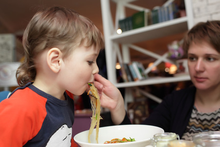 eating noodles: Son eating noodles from her mother