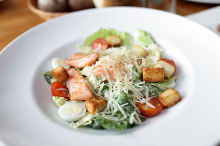 Caesar Salad with salmon , cherry tomatoes in a bowl photo