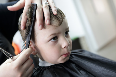 Portrait of a serious kid at hairdresser salon photo