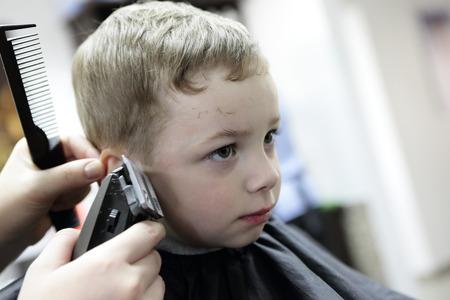 Boy having a haircut at the barbershop photo