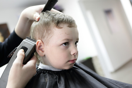 Portrait of a serious boy at the barbershop photo