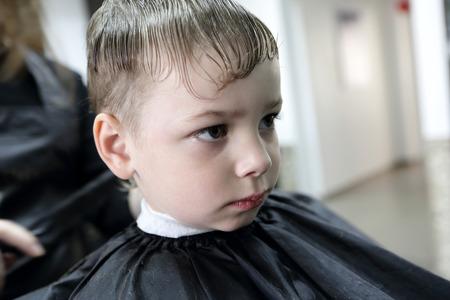 Serious boy having a haircut at the barbershop photo