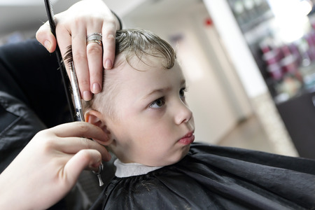 Barber cutting hair of a serious boy at the barbershop photo