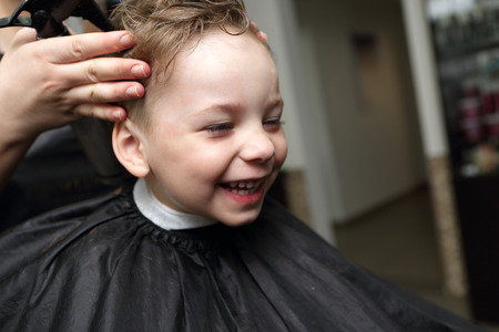 Portrait of a laughing boy at the barbershop photo