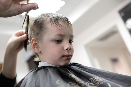 Barber cutting hair of a kid at the barbershop photo