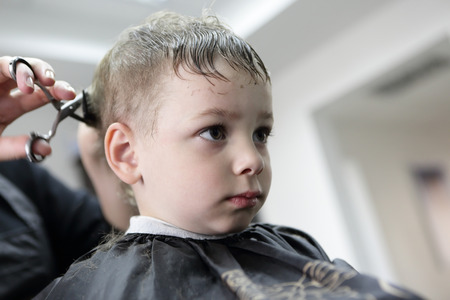 Barber cutting hair of a child at the barbershop photo