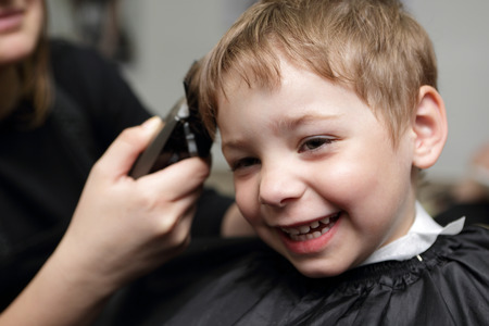 Portrait of happy child at the barbershop photo