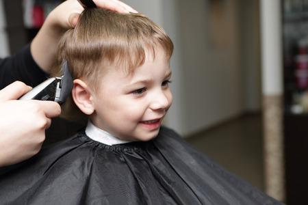 Portrait of happy kid at the barbershop photo