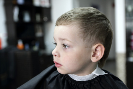 Portrait of a serious child at hairdresser salon photo