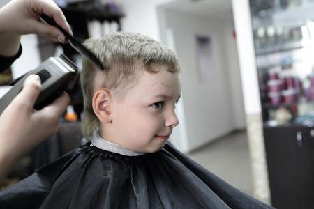 Kid having a haircut at the barbershop photo