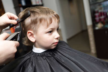 Serious child having a haircut at the barbershop photo