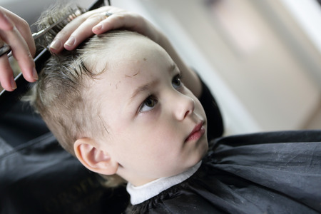Barber cutting hair of a boy at the barbershop photo