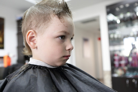 Child having a haircut at the barbershop photo