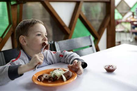 niños sentados: Niño que come el kebab con cebollas en el café Foto de archivo