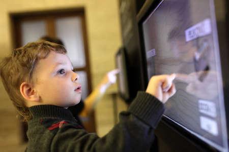 ni�o empujando: Ni�o que usa la pantalla t�ctil interactiva en un museo