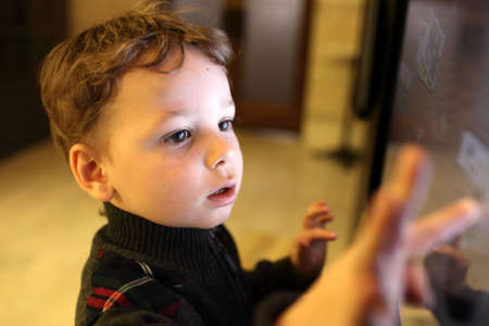 kids playing video games: Kid using interactive touch screen in a museum Stock Photo