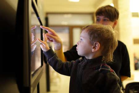 mujer hijos: Madre con su hijo que usa la pantalla t�ctil en un museo