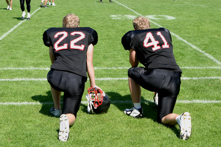 tricot: Two american football players kneeing at the sideline of the matchfield and waiting for their participation in the game
