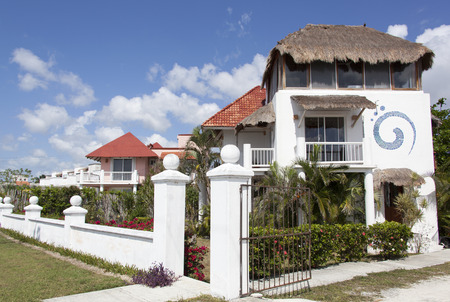 characteristic: Residential houses with characteristic straw roofs in San Miguel resort town (Cozumel, Mexico).