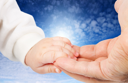 Baby hand holding adult hand