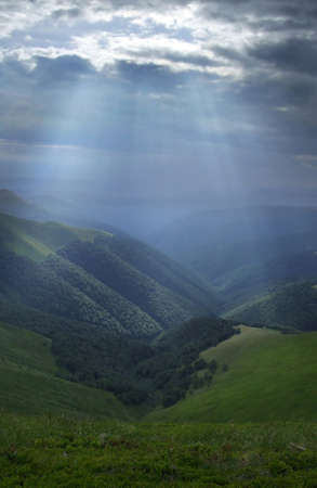 Mountain valley lightened by bright sunrays Stock Photo