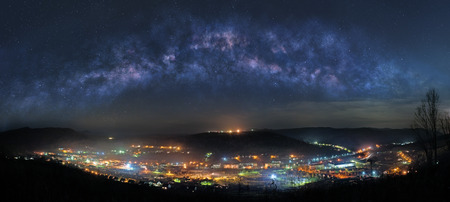 Panoramic picture of mountain town at night with majestic Milky Way on the sky photo