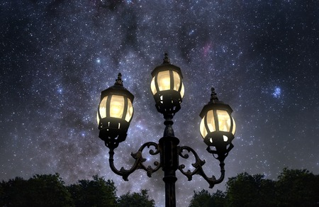 Vintage looking lamp post against beautiful starry sky photo