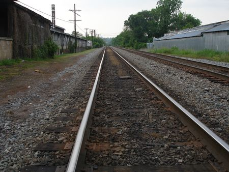 Southbound train tracks between rundown warehouses just after the 6:05 train passed. Stock Photo - 440344