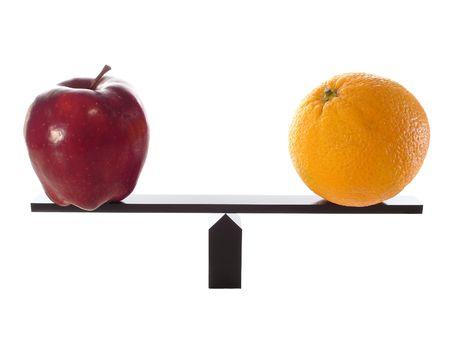 unequal: Comparando manzanas con naranjas en una balanza Manga aislados en blanco.  Foto de archivo