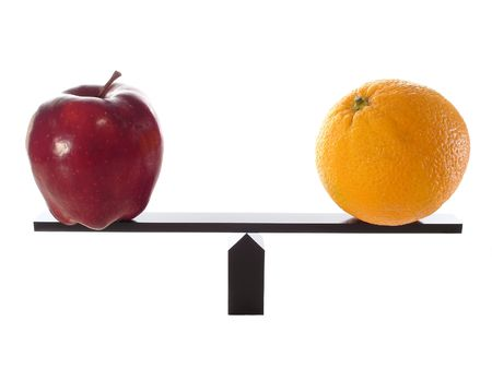 Comparing Apples to Oranges on a Balance Beam isolated on white. Stock Photo