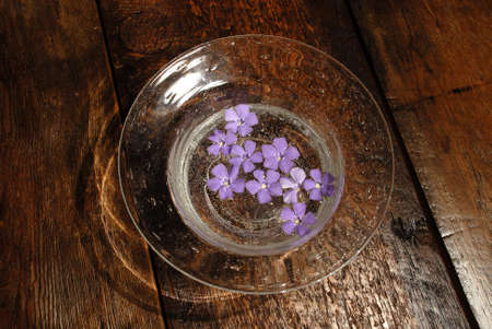 multiples: Purple flowers in bowl in bowl on wooden table Stock Photo