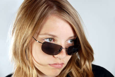 Young pre-teen girl, with attitude looking over top of sunglasses to the side.