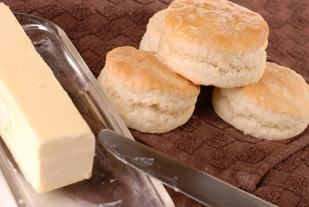 Homemade biscuits baked and dripping with butter ready to eat laying on a brown towel with a butter dish of butter, and a knife along side.