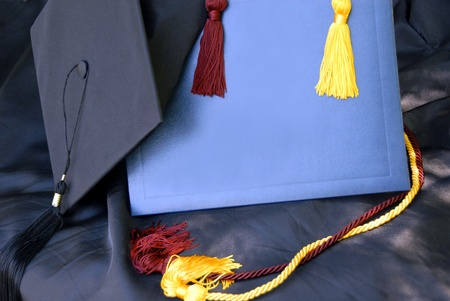Display of graduation cap and gown, mortar board, diploma cover, and tassels with room for your school emblem, and text.