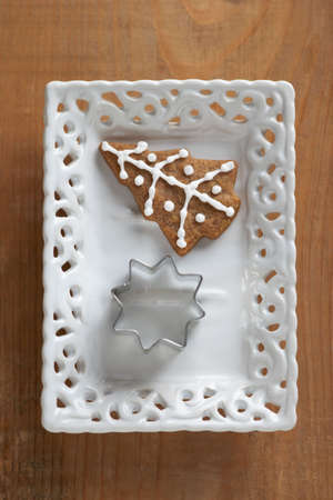 Gingerbread cookie and cookie cutter on plate photo