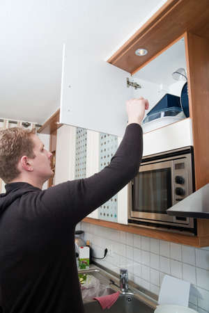 kitchen cupboard: Young man in kitchen opening a kitchen cupboard Stock Photo