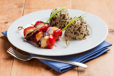 Bamboo skewers with chicken filet, red pepper and onions. Grilled with wild rice on the side photo