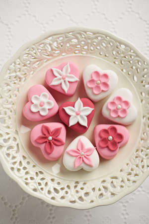 Fondant-covered petit fours on vintage style cake stand photo