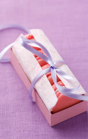 Pink macarons in gift box with ribbon. No one is viewable in the image photo