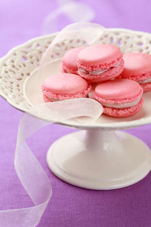 Pink macarons piled up on vintage cake stand. No one is viewable in the image photo