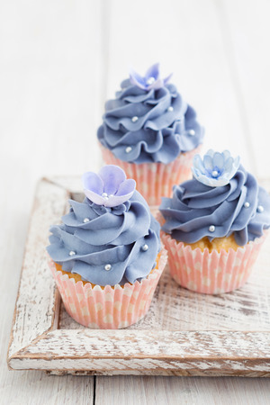 Three purple cupcakes with buttercream frosting swirl, silver pearls and edible flowers Stock Photo