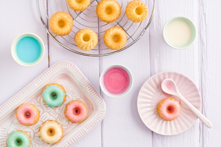 cake decorating: Iced mini bundt cakes with icing, a tray and a spoon Stock Photo