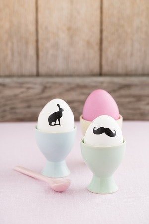 egg cups: Easter eggs with bunny  and moustache silhouettes in egg cups