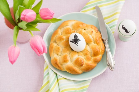 butterfly knife: Hipster Easter breakfast table with moustache Easter egg, tulips and sweet braided yeast bread